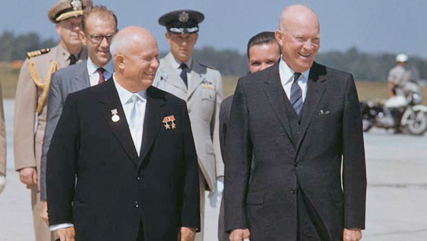 Color photograph of President Dwight D. Eisenhower and Soviet leader Nikita Khrushchev walking side by side. Several men in military uniform stand behind them.