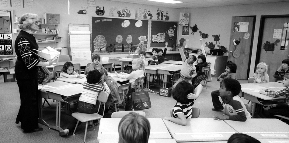 Black and white photograph of a classroom at Glen Forest Elementary School in November 1981. A teacher is leading a class of what look to be second or third graders. The children are very engaged in the lesson and have their hands up in the air waiting to answer.